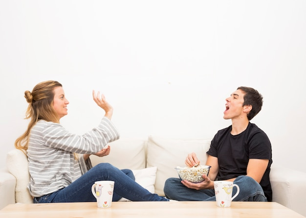 Woman throwing popcorn in man's mouth sitting on sofa