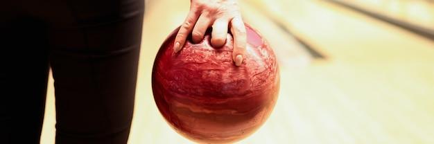 Woman throwing red bowling ball on lane closeup