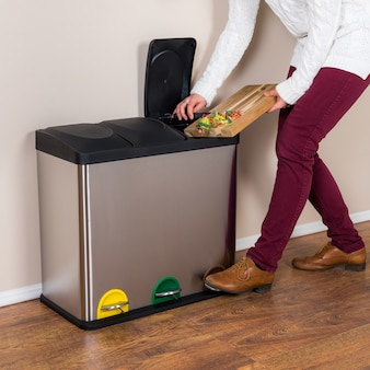 無駄な食べ物を鋼のゴミ箱に投げる女性