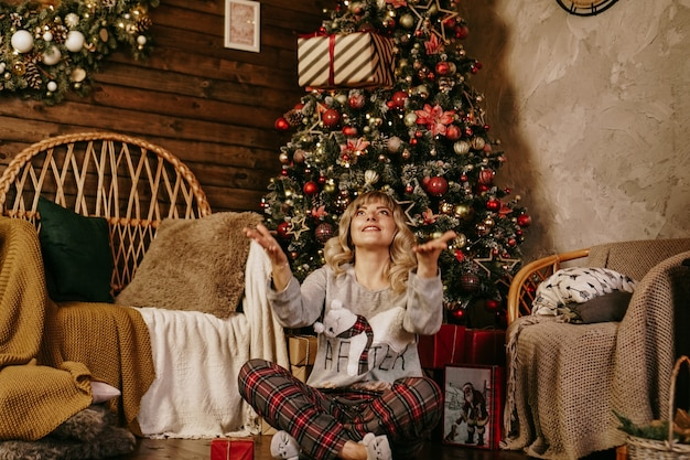 贈り物を投げる女性、新年のコンセプト、クリスマスの居心地の良いインテリア