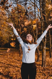 Woman throwing yellow leaves in the air - autumn park