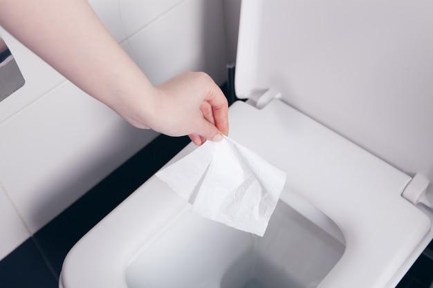 여자는 화장실에 냅킨을 던졌습니다.
