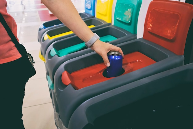 Woman throws aluminum can into one from four bins for sorting garbage