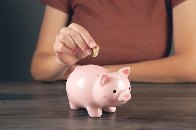 Woman throws a coin into a piggy bank