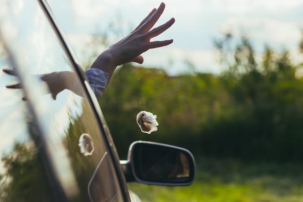 Женщина выбрасывает мусор из окна машины