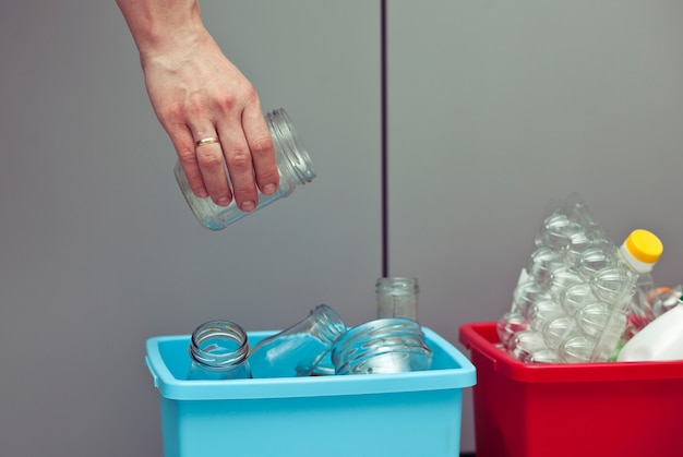 The woman throws the glass bottle to the one of four container for sorting garbage