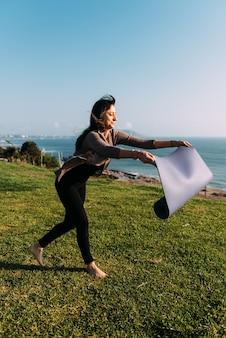 女性は屋外でヨガをするために草の上に彼女のマットを投げます