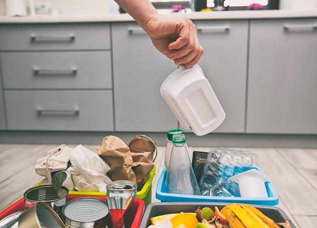 Женщина выбрасывает пластиковую тару в один из четырех контейнеров или сортирует мусор