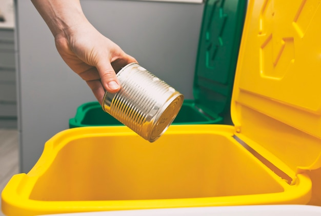 The woman throws the tin can to the one of three container for sorting garbage