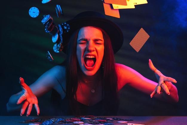 여자는 빨간색과 파란색 불빛과 함께 카지노에서 포커 테이블에서 카드와 칩을 던졌습니다