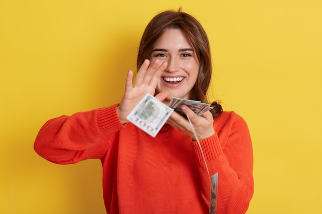 Woman throws up cash, lottery winner with very happy expression, smiling, lady with banknotes indoor, dark haired girl with her currency, has reward.