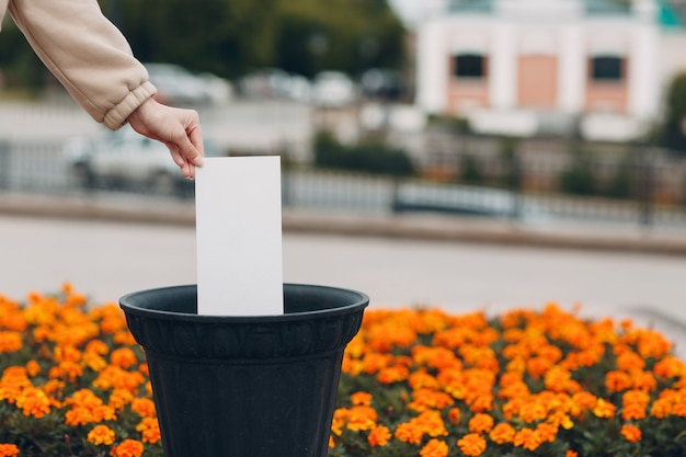 Женщина бросает белый лист бумаги без надписи в мусорное ведро. шаблон для слов с копией пространства.