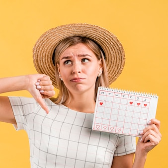 Woman thumbs down the period calendar