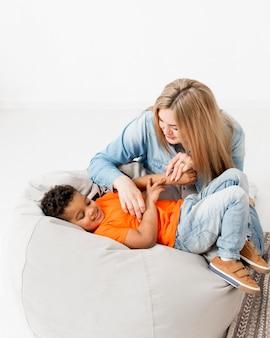 Donna che solletica giovane ragazzo felice