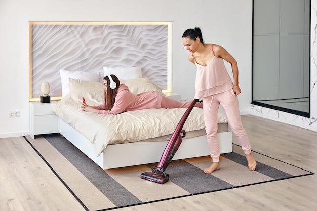 Женщина убирает в спальне пылесос, пока ее дочь слушает музыку на смартфоне через наушники, лежа на животе в постели.