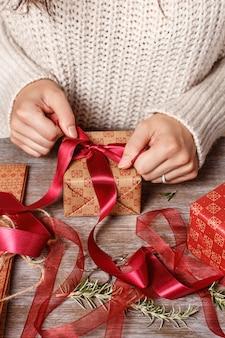 Женщина завязывает ленточный бант и упаковывает подарки крупным планом