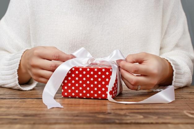 Женщина завязывает ленточный бант на завернутом подарке крупным планом
