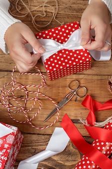 Женщина завязывает ленточный бант на обернутом подарке