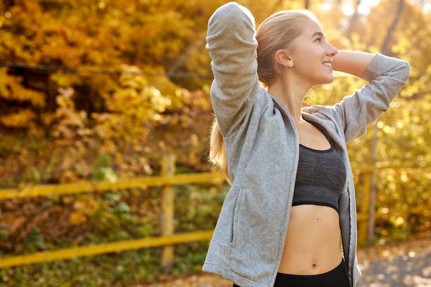 女性は、スポーティーな服を着て、走る前にポニーテールで髪を結びます