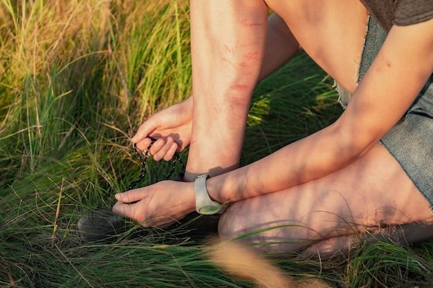 Женщина завязывает шнурки кроссовок. крупным планом изображение женских рук и ног в царапинах и синяках в натуральной зеленой траве, связывая шнурки походной обуви