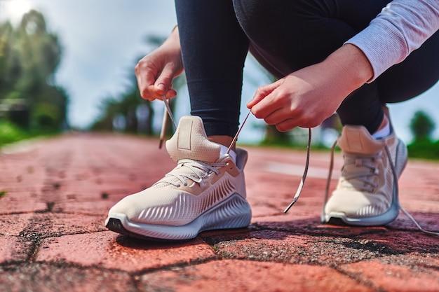 Женщина завязывает шнурки на кроссовках
