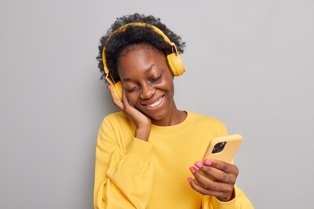 女性は笑顔を傾けて喜んでワイヤレスヘッドフォンで音楽を聴きます灰色に分離された黄色のジャンパーに身を包んだスマートフォンを保持します