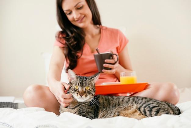 Женщина ласкает свою кошку и завтракает. она в своей спальне