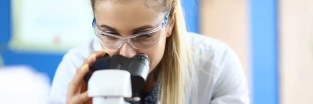 실험실에서 여자는 현미경을 통해 보이는