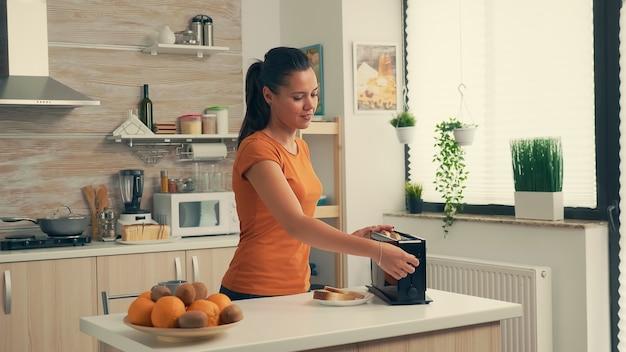 朝食のために朝にパンを乾杯する女性。おいしい朝食にパントースターを使用している主婦。居心地の良いインテリアで健康的な朝、おいしい家庭料理の準備