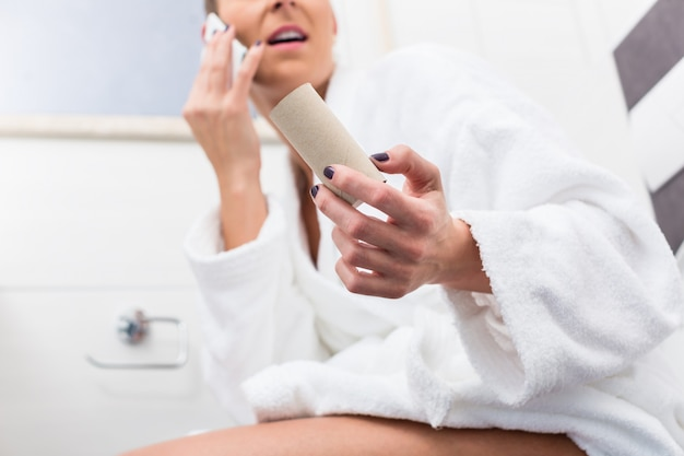 Woman on toilet complaining via phone about lack of paper