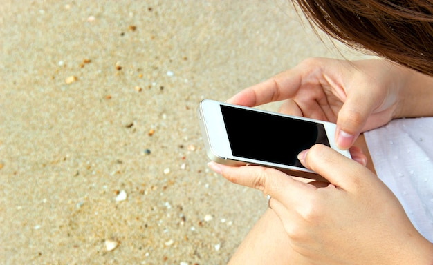 Woman touch screen cell phone on sand