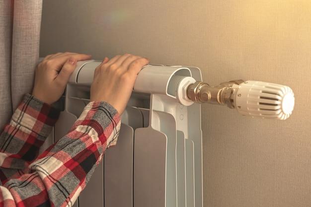 Женщина трогает радиатор обогревателя для обогрева дома, фото фона терморегулирования