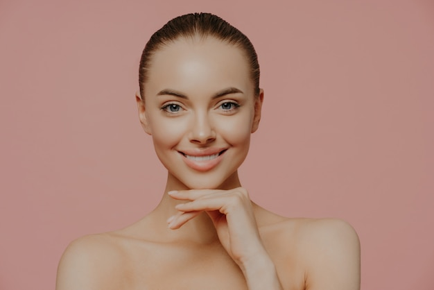 Woman touches chin gently, enjoys flawless of skin after beauty procedures, poses nude, has natural makeup, isolated on pink