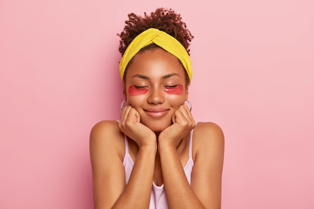 Woman touches chin, wears collagen patches for puffiness, reduces fine lines, has curly hair, keeps eyes closed, shows her healthy dark skin, isolated on pink wall