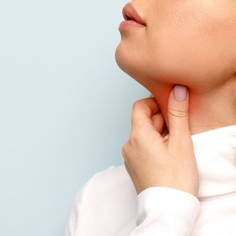 Woman touches fingers of sore throat. thyroid gland, painful swallowing, tonsillitis, laryngeal swelling