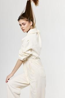 女性は手と白いジャンプスーツのファッショナブルな服のモデルで頭の上の髪に触れます。高品質の写真