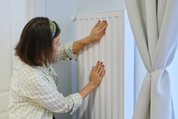 Woman touches heating radiator in home interior