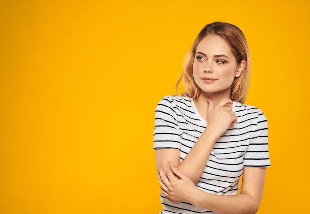 여자는 노란색 배경 미소 노란색 배경 모델 패션에 손으로 자신을 만집니다. 고품질 사진