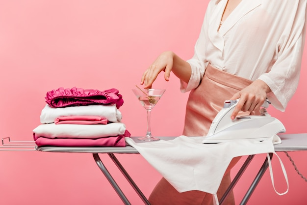 Woman touches martini glass and ironing white blouse
