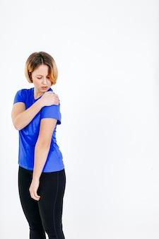 Женщина, касаясь больного плеча