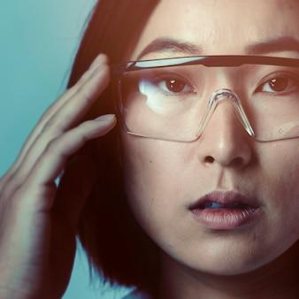 Donna che tocca la tecnologia futuristica degli occhiali intelligenti di ar