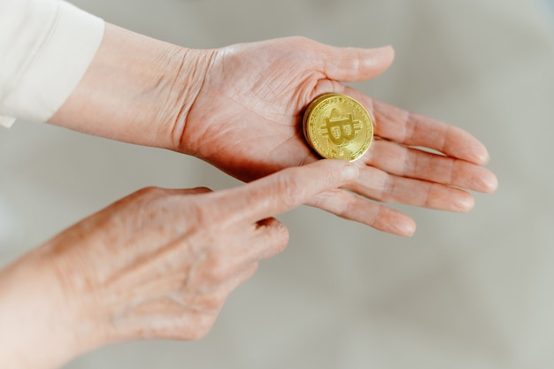Woman touching bitcoin in her palm photo with a copyspace
