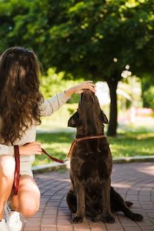 공원에서 강아지의 입을 만지는 여자