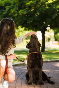 Woman touching dog's mouth in park