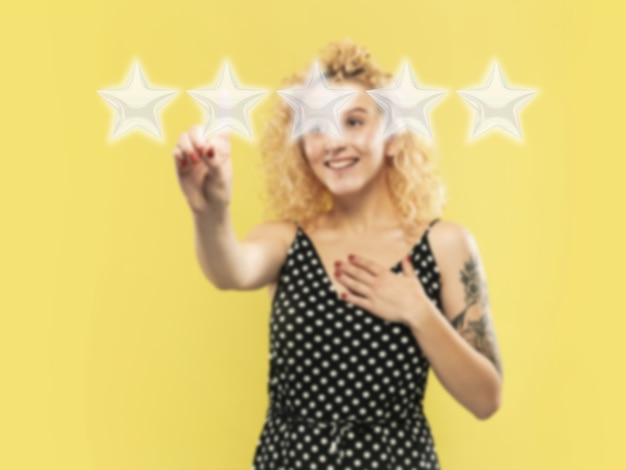 Woman touching five star symbol to increase rating of company app or service