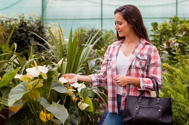 Woman touching flowers in greenhouse