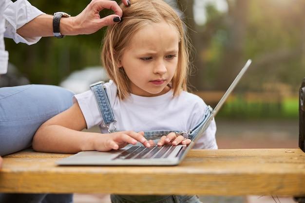 여자 아이가 화면 노트북을보고있는 동안 야외에서 귀여운 매력적인 딸의 머리를 만지고 여자