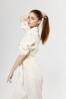 彼女の頭の髪に触れる女性とファッショナブルな服のジャンプスーツスタイルのクロップドビュー
