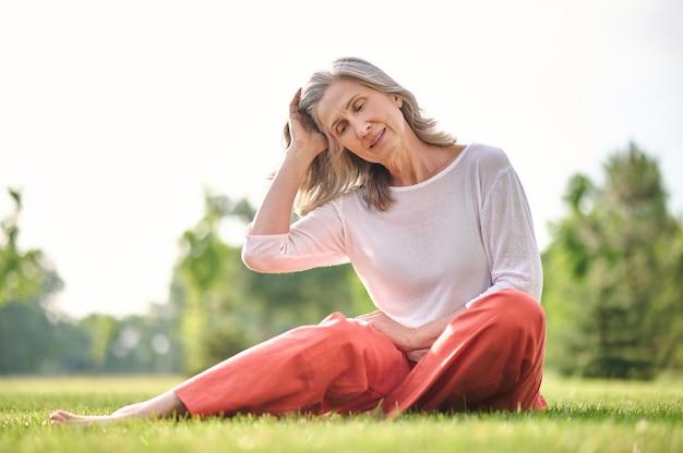 Женщина трогает волосы, сидя на траве