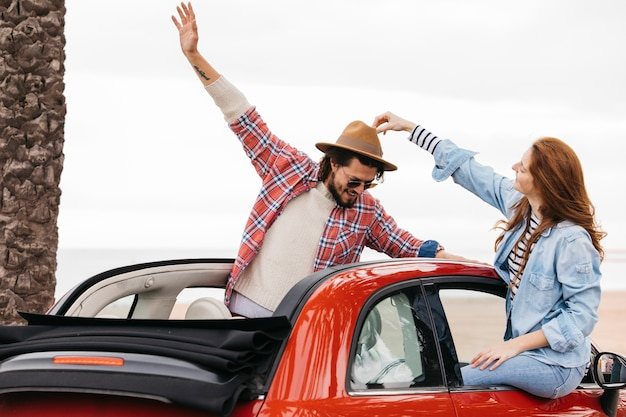 Woman touching hat on man's head and leaning out from car